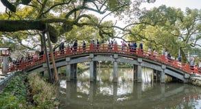 De toeristen lopen de kruising van de Rode brug van Dazaifu-Heiligdom Royalty-vrije Stock Fotografie