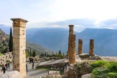 De toeristen lopen door runis in oud Delphi met vallei en bergen op de achtergrond op mistige dag Delphi Greece 1 8 2018 royalty-vrije stock foto's