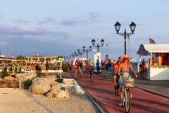 De toeristen lopen en berijden op elektrische cycli en fietsen op prome Stock Afbeeldingen