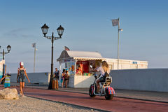 De toeristen lopen en berijden op elektrische cycli en fietsen op prome Royalty-vrije Stock Foto's