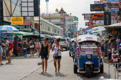 De toeristen lopen langs de Weg van Khao San van het backpackertoevluchtsoord en tuktuk in Bangkok, Royalty-vrije Stock Foto