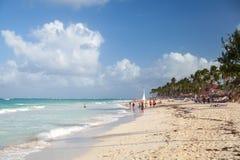 De toeristen lopen langs een strand van de toevlucht van Punta Cana Royalty-vrije Stock Foto
