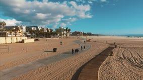 De toeristen lopen langs de weg op het strand dichtbij Santa Monica-pijler stock videobeelden