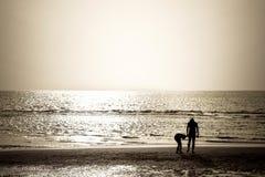 De toeristen lopen op het strand Stock Afbeeldingen
