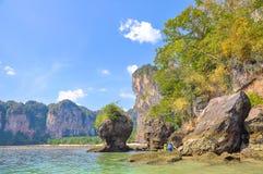 De toeristen lopen op het water langs de klippen aan het strand Stock Afbeeldingen