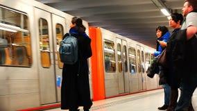 De toeristen met gadgets naderen de naderbij komende metro trein stock videobeelden