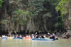 De toeristen met gidsen zwemmen in opblaasbare kano's onder de reuzeklippen Toeristen die in Ao Phang Nga nationaal park, Thailan royalty-vrije stock foto's