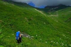 De toeristen met grote rugzakken reizen in de bergen op het concept levensstijlsport beklimmend achtergrond Stock Afbeelding
