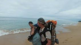 De toeristen met rugzakken gaan op de kust stock video