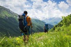 De toeristen met wandelingsrugzakken in berg wandelen in Svaneti op de zomerdag De jonge kerels gaan langs het voetpad door de be stock afbeeldingen