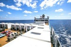 De toeristen ontspannen en nemen een zonbad op het hogere dek van een cruise Stock Foto's