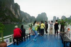 De toeristen op een boot in Ha snakken Baai Vietnam stock foto's