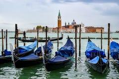 De toeristen op gondelboot berijden tussen lege gedokte gondels en Kerk van San Giorgio Maggiore op achtergrond stock foto's