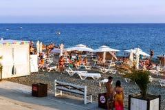 De toeristen op het strand van de kust van de Zwarte Zee, zwemmen en zonnebaden Royalty-vrije Stock Foto's