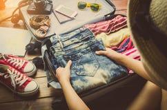 De toeristen pakken bagage voor reis in Stock Foto's