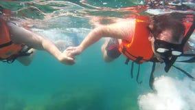 De toeristen in reddingsvesten drijven het onderwater Snorkelen stock videobeelden