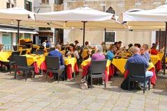 De toeristen rusten bij de lijsten in een openluchtkoffie in Venetië, Italië Stock Foto