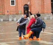 De toeristen in San Marco regelen met vloed, Venetië, Italië Stock Afbeeldingen