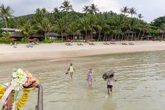 De toeristen schepen een passagiersboot van het strand in stock foto's