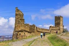 De toeristen van de achtergrondlandschapsmening lopen in een Sudak-vesting in het midden van de ruïnes van oude torens in de Krim royalty-vrije stock afbeeldingen
