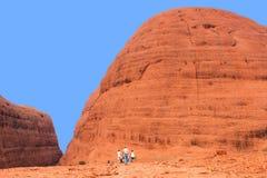 De toeristen wandelen langs Olgas in Australië Stock Foto's