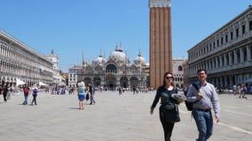 De toeristen worden gefotografeerd op achtergrond St Mark Cathedral tijdens gang op vierkant en vogelsvlieg stock videobeelden