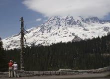 De toeristen zetten Regenachtiger op Stock Afbeeldingen