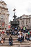 De toeristen zitten door Piccadilly Circus in Londen Stock Fotografie