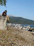 De toeristen zitten langs Meer Baikal Stock Afbeeldingen