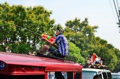 De toeristen zitten op busdak voor het vieren Songkran (Thais nieuw jaar/water festival) in de straten Stock Afbeeldingen