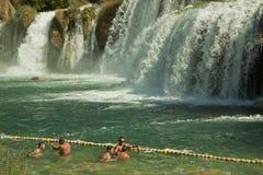 De toeristen zwemmen bij Krka-watervallen, Kroatië Stock Fotografie