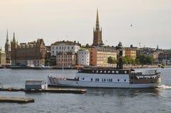 De toeristenboot kruist door Stockholm's oude stad op het beroemde die gebied van Gamla Stan dicht door archaïsch gebouwen word royalty-vrije stock afbeelding
