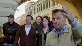 De toeristengroep met gids komt dicht bij de camera en bekijkt erachter het voorwerp Achtergrond van de oude bouw met boog stock footage