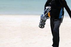 De toeristenmens loopt, houdend een babywandelwagens en bagage op het witte zandstrand stock afbeeldingen