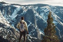 De toeristenmens zich op de bergbovenkant bevinden met rugzak en de camera die en genieten van de mening na wandeling Royalty-vrije Stock Afbeeldingen