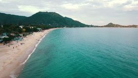De toeristenmensen die op overzees strand op achtergrondpalm en heuvelantenne rusten bekijken stock footage