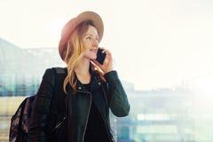 De toeristenvrouw in hoed met rugzak bevindt zich bij luchthaven en spreekt op celtelefoon Meisjestribunes, gebruiks digitaal gad stock foto's