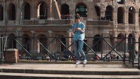 De toeristenvrouw neemt selfie foto's in Colosseum in Rome, Italië met smartphone Het meisje reduceert de stappen Langzame Motie stock video