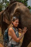 De toeristenvrouw stelt met volwassen olifant royalty-vrije stock afbeeldingen