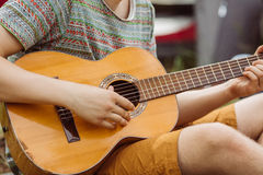 De toeristenzitting in de tent, speelt de gitaar en zingt liederen Stock Foto's