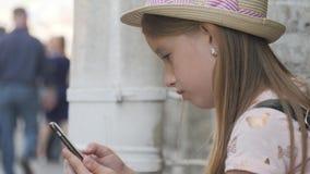 De toeristenzitting die van het tienermeisje informatie over een smartphone op vakanties op de stadsstraat zoeken Technologie, vr stock videobeelden
