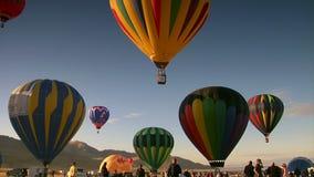 De toeschouwers letten op aangezien de hete luchtballons in de hemel stijgen stock videobeelden