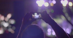 De toeschouwersmens maakt een panoramische foto van stadium met schijnwerpers via smartphone bij openluchtmuziekoverleg stock videobeelden