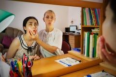 De toespraaktherapeut onderwijst een jong meisje de correcte uitspraak van toespraak stock afbeelding