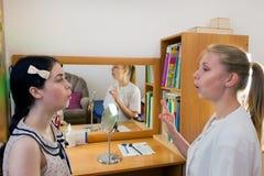 De toespraaktherapeut onderwijst een jong meisje de correcte uitspraak van toespraak op spiegelachtergrond royalty-vrije stock foto