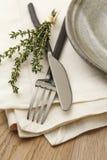 De toevallige fijne eettafel die met natuurlijke, organische stijlvork, mes, servet en plaat plaatsen, accentueerde met een twijg Stock Afbeeldingen
