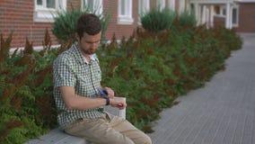 De toevallige geklede mens zit op de bank en gebruikt zijn slimme horloge en smartphone stock videobeelden