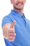 De toevallige jonge mens biedt handdruk aan stock foto's