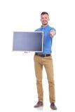 De toevallige jonge mens houdt bord en richt op u Stock Foto
