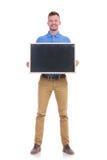 De toevallige jonge mens houdt een klein bord Royalty-vrije Stock Foto